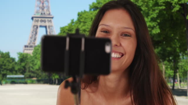 Woman tourist sightseeing in Paris, France using selfie stick near Eiffel Tower