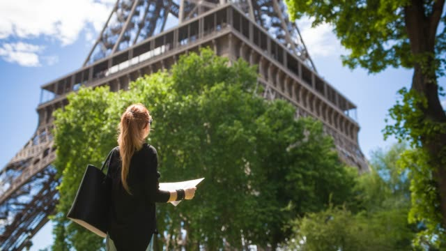 woman tourist standing under eiffel tower and admiring it - eiffel tower stock videos & royalty-free footage