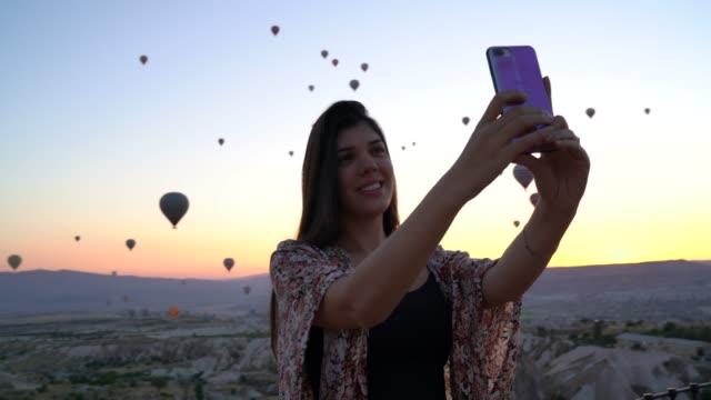 vídeos y material grabado en eventos de stock de mujer turista tomando un selfie en capadocia, turquía - una sola mujer joven