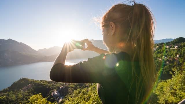 Tourist fotografiert Panoramablick auf den italienischen Comer See und das Dorf am See mit europäischen Alpen im Hintergrund