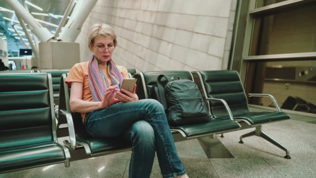 a woman, tourist, using a smartphone when she sitting and waiting for a departure in the airport lounge. approaching camera motion. - 55 59 years stock videos & royalty-free footage