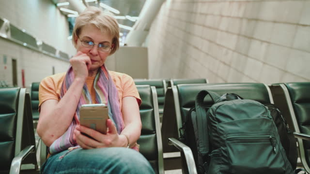 a woman, tourist, using a smartphone when she sitting and waiting for a departure in the airport lounge. camera moving back (pull motion). - 55 59 years stock videos & royalty-free footage