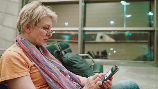 a woman, tourist, using a smartphone when she sitting and waiting for a departure in the airport lounge. - 55 59 years stock videos & royalty-free footage
