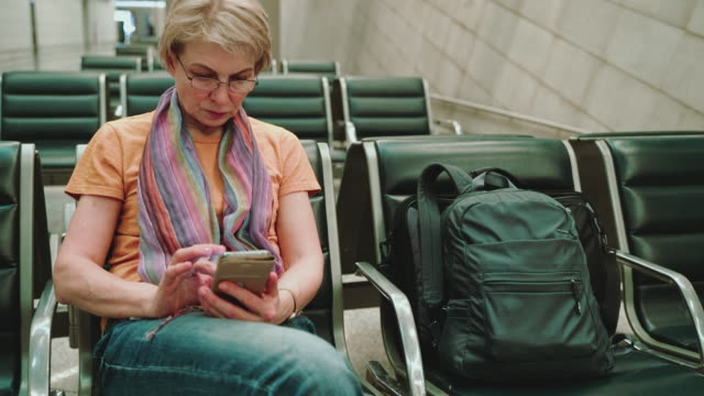 a woman, tourist, using a smartphone when she sitting and waiting for a departure in the airport lounge. descending camera motion. - 55 59 years stock videos & royalty-free footage