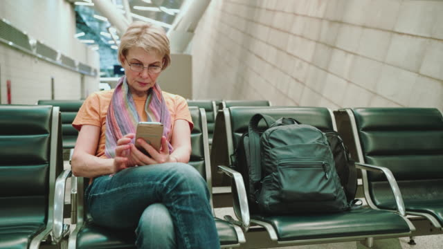 a woman, tourist, using a smartphone when she sitting and waiting for a departure in the airport lounge. pulling camera motion. - 55 59 years stock videos & royalty-free footage
