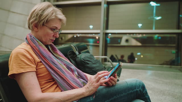 a woman, tourist, using a smartphone when she sitting and waiting for a departure in the airport lounge. panning camera motion. - 55 59 years stock videos & royalty-free footage