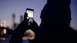 Woman tourist using smartphone take a photo panorama of river