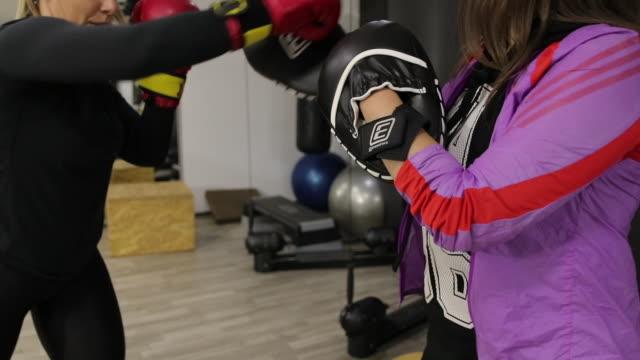vidéos et rushes de femme formation de boxe avec l'instructeur au gymnase - seulement des jeunes femmes
