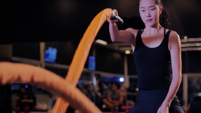 woman training doing battling rope workout working out arms and cardio for gym exercises.fitness people exercising with battle ropes at gym.sport prep - chinese ethnicity stock videos & royalty-free footage