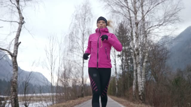 woman training  for marathon by running on a walkway in nature in freezing temperatures - wide stock videos and b-roll footage