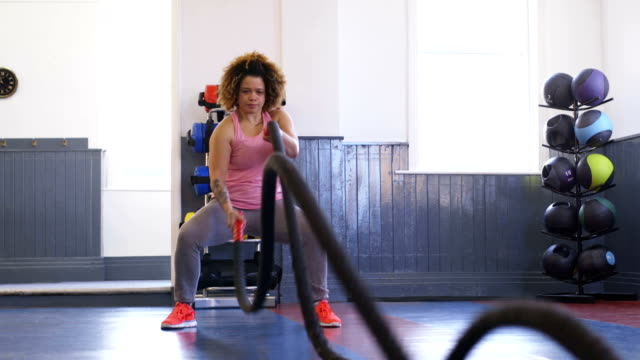 woman training in gym with battle ropes - cross trainer stock videos and b-roll footage