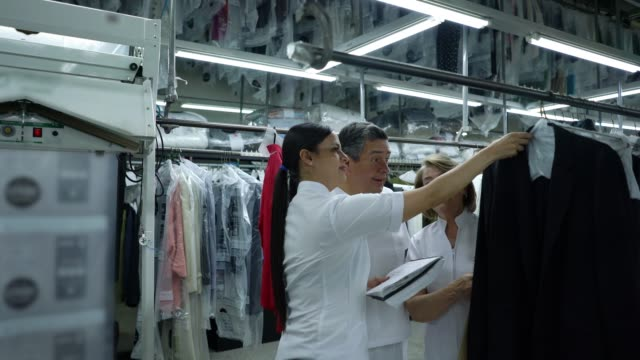 woman training mature adults explaining something holding a notepad and looking at clothes on rack at an industrial laundry - lavanderia pubblica video stock e b–roll