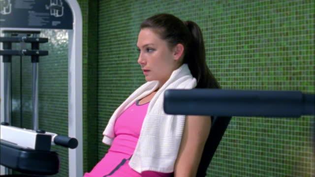 vídeos de stock, filmes e b-roll de ds ms woman training on weight machine in gym, new york city, new york, usa - cabelo preso