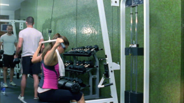 ds ms woman training on weight machine in gym, new york city, new york, usa - female with group of males stock videos & royalty-free footage