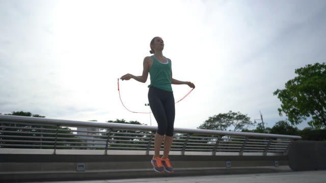 woman training outdoors jumping rope - skipping stock videos & royalty-free footage