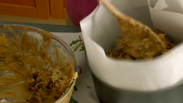 Woman Transfers Christmas Fruit Cake Mixture to a Lined Cake Tin