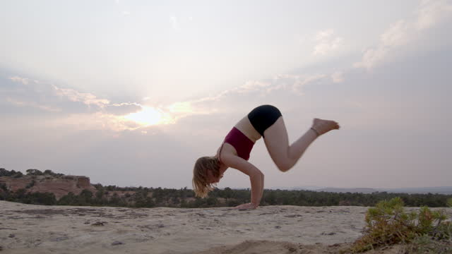 stockvideo's en b-roll-footage met woman transitioning from flying pigeon to plank yoga pose outside in the mountains near grand junction and fruita colorado with a dramatic sunset in the background - in kleermakerszit