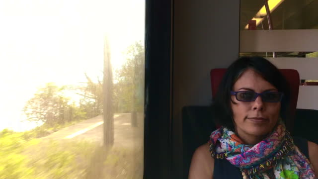 Woman Travel in a Train and Enjoy the View over Alpine Lake with Sunshine