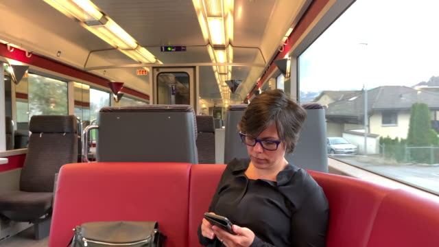 vidéos et rushes de woman travel in a train and using phone in city - wagon