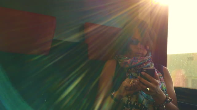 woman travel in a train and using smartphone with sunbeam - interno di treno video stock e b–roll