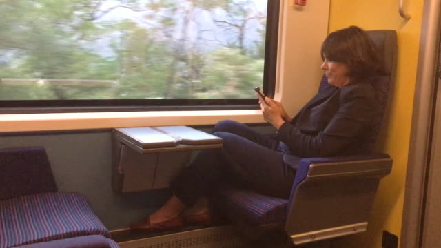 woman travel inside a train wagon and using her smartphone - vehicle seat stock videos & royalty-free footage