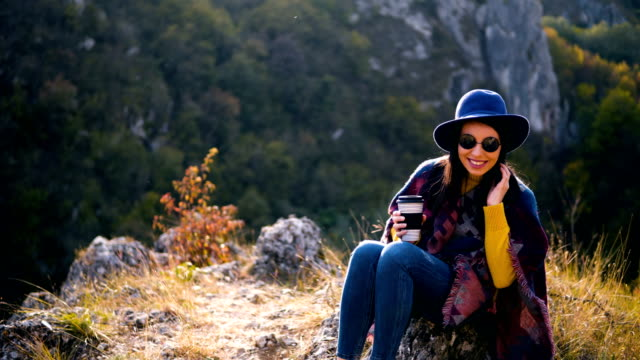 woman traveler drinks coffee with a view of the mountain landscape. a young tourist woman drinks a hot drink from a cup and enjoys the scenery in the mountains. trekking concept - coffee drink stock videos & royalty-free footage