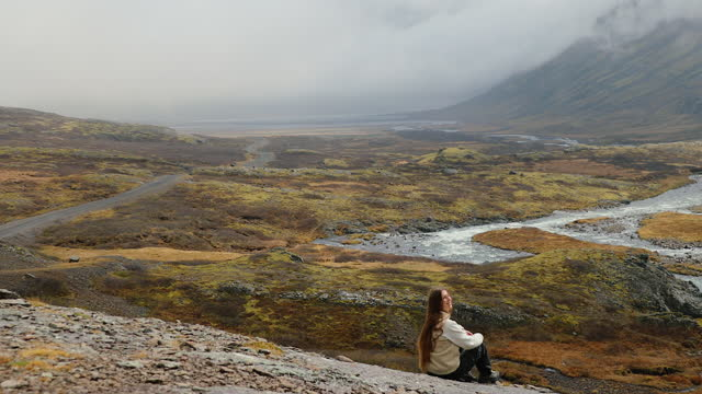 woman traveler enjoying the view of the scenic mountain landscape in iceland - horizon stock videos & royalty-free footage