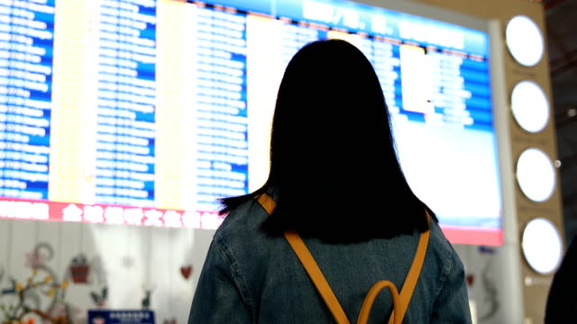 Woman traveler looking at flight information screen in airport