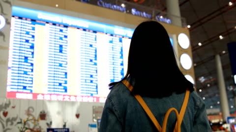 vídeos de stock, filmes e b-roll de viajante de mulher olhando para a tela de informações de voo no aeroporto - sinalização digital