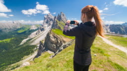 Woman traveler on Seceda mountain in Dolomites mountains photographing breathtaking view