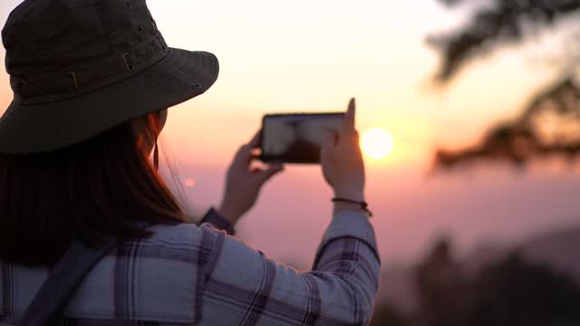 woman traveler scatta una foto un posto meraviglioso con tramonto sulla montagna - tourism video stock e b–roll