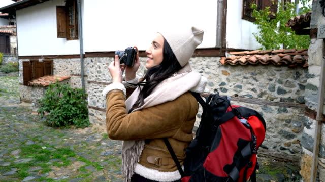 vídeos de stock e filmes b-roll de woman traveler taking pictures while walking in small village. - bairro antigo
