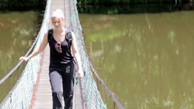 woman traveler walking over a suspension bridge, borneo - sabah state stock videos and b-roll footage