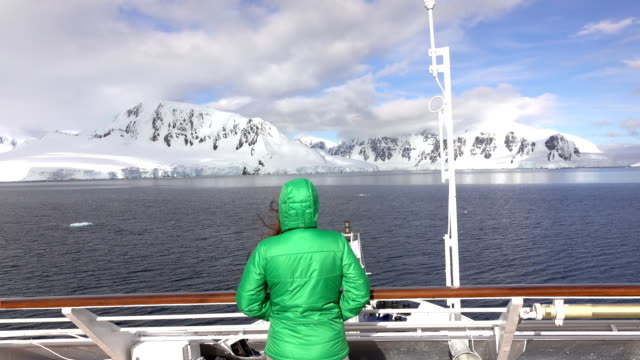 woman traveler watches neumeyer channel wiencke island mountains antarctica - antarctica people stock videos & royalty-free footage