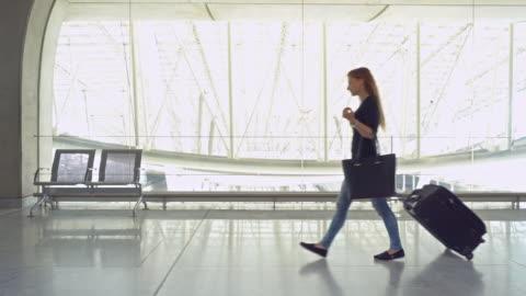 vídeos de stock, filmes e b-roll de viajante de mulher com bagagem andando através do terminal do aeroporto - mala de rodinhas