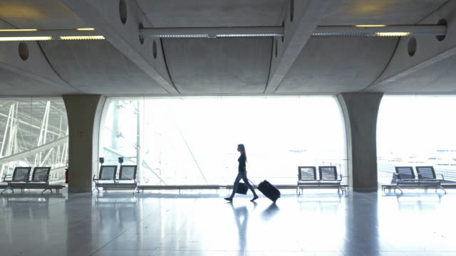 woman traveler with luggage walking through concourse - wheeled luggage stock videos and b-roll footage