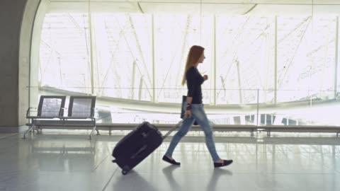 vídeos de stock, filmes e b-roll de viajante de mulher com bagagem andando pelo corredor - mala de rodinhas