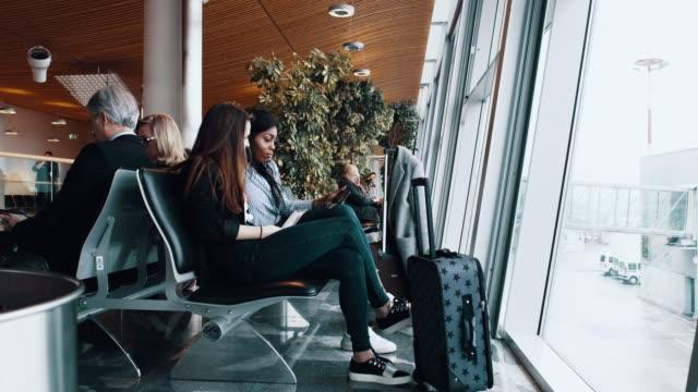 stockvideo's en b-roll-footage met vrouw reizigers met bagage te wachten op de luchthaven - spelletjesavond