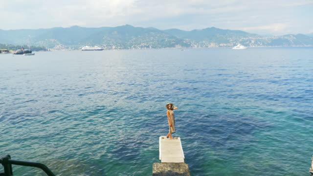 a woman traveling alone on a dock over the mediterranean sea in italy, europe. - slow motion - cappello video stock e b–roll
