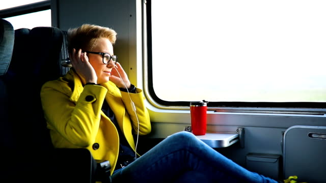 woman traveling by train with favorite music - railing stock videos & royalty-free footage