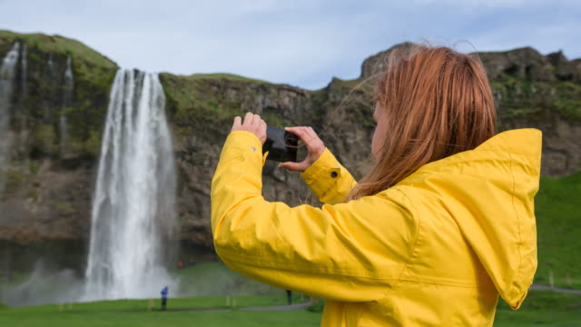 Woman traveling Iceland, taking pictures of natural landmarks