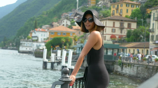 a woman traveling in a luxury resort town near lake como, italy, europe. - slow motion - cappello video stock e b–roll