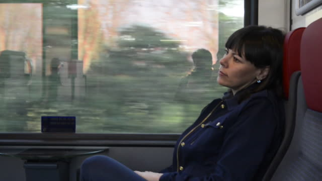 vídeos de stock, filmes e b-roll de woman traveling in a train - jaqueta jeans