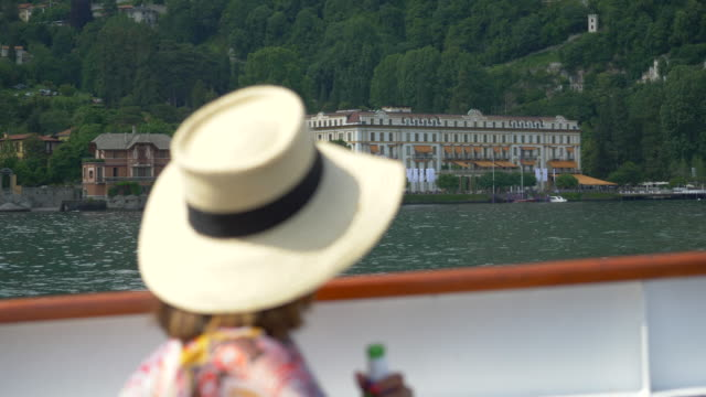 a woman traveling with hat drinks beer on ferry on lake como, italy, europe. - slow motion - alchol video stock e b–roll