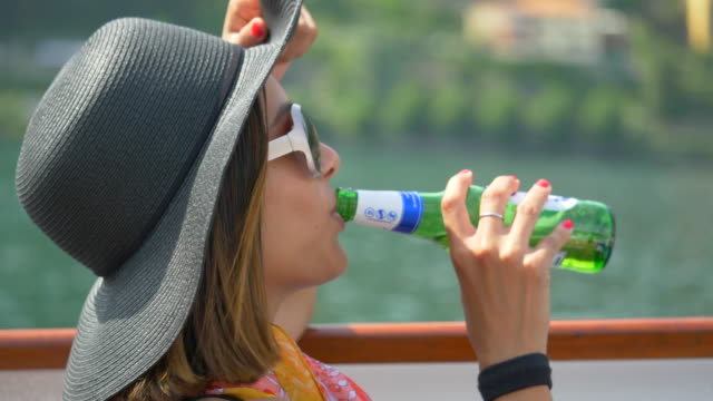 A woman traveling with hat drinks beer on ferry on Lake Como, Italy, Europe. - Slow Motion