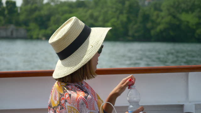 a woman traveling with hat drinks bottled water on ferry on lake como, italy, europe. - slow motion - drinking water stock videos & royalty-free footage