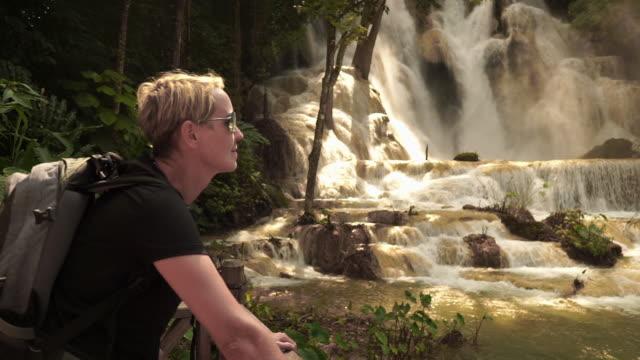 stockvideo's en b-roll-footage met vrouw traveller op kuang si waterval, luang prabang, laos - kort haar