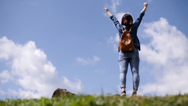 Woman traveller happy with her journey with blue sky , slow motion