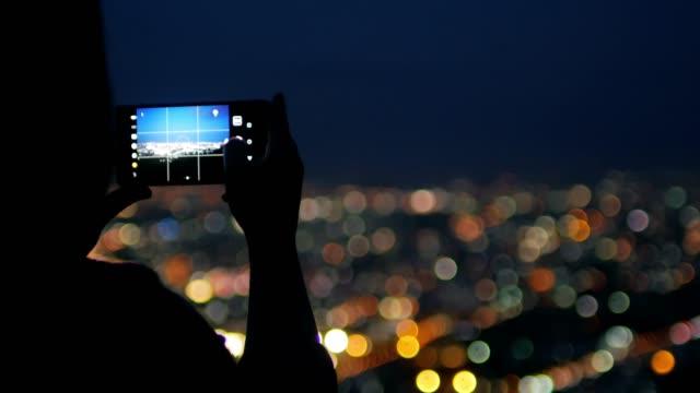vídeos y material grabado en eventos de stock de foto mujer viajero tomar ciudad por teléfono inteligente en la noche - photography themes