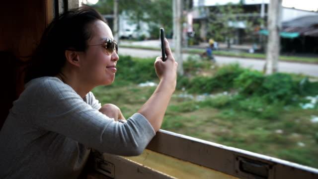 電車で携帯電話で写真を撮る女性旅行者 - デジタル一眼レフカメラ点の映像素材/bロール